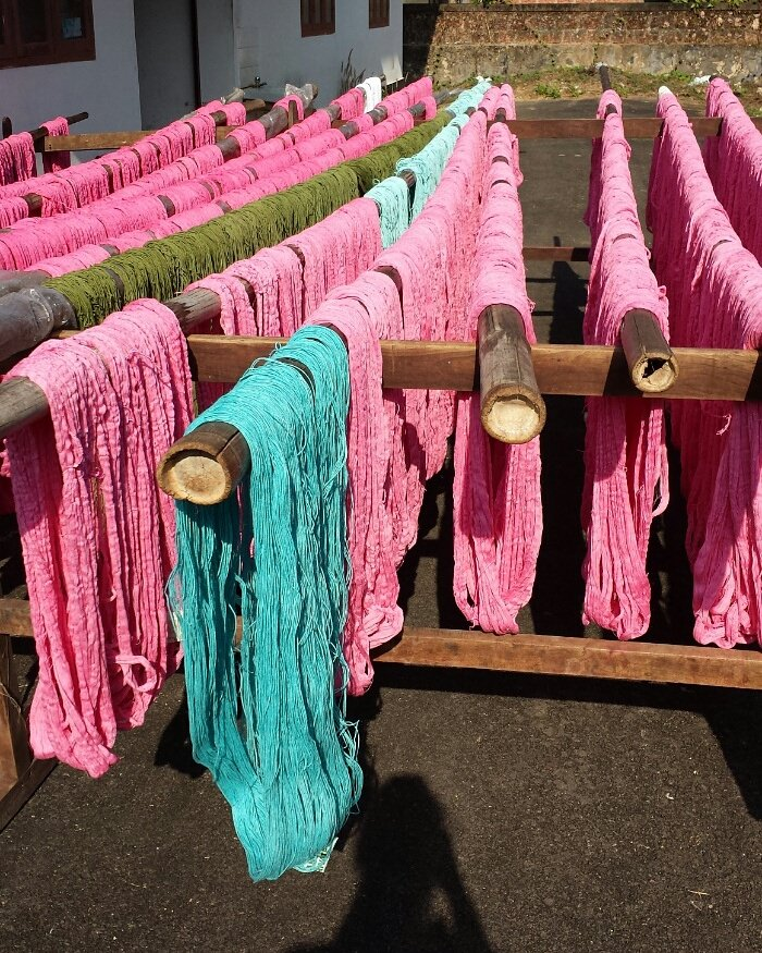 Once the yarn is fully dyed, the workers take the bamboo poles and place them outside.